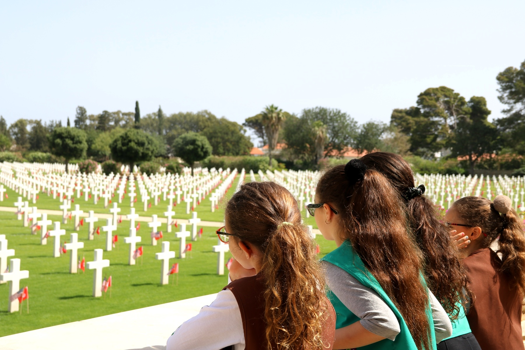 Girl Scouts from Brownie Troop 40502 and Junior Troop 40503 look out over the North Africa American Cemetery after the Memorial Day ceremony in Carthage, Tunisia, May 28, 2018. (Photo by Zouhaier SFAXI, U.S. Embassy Tunis)