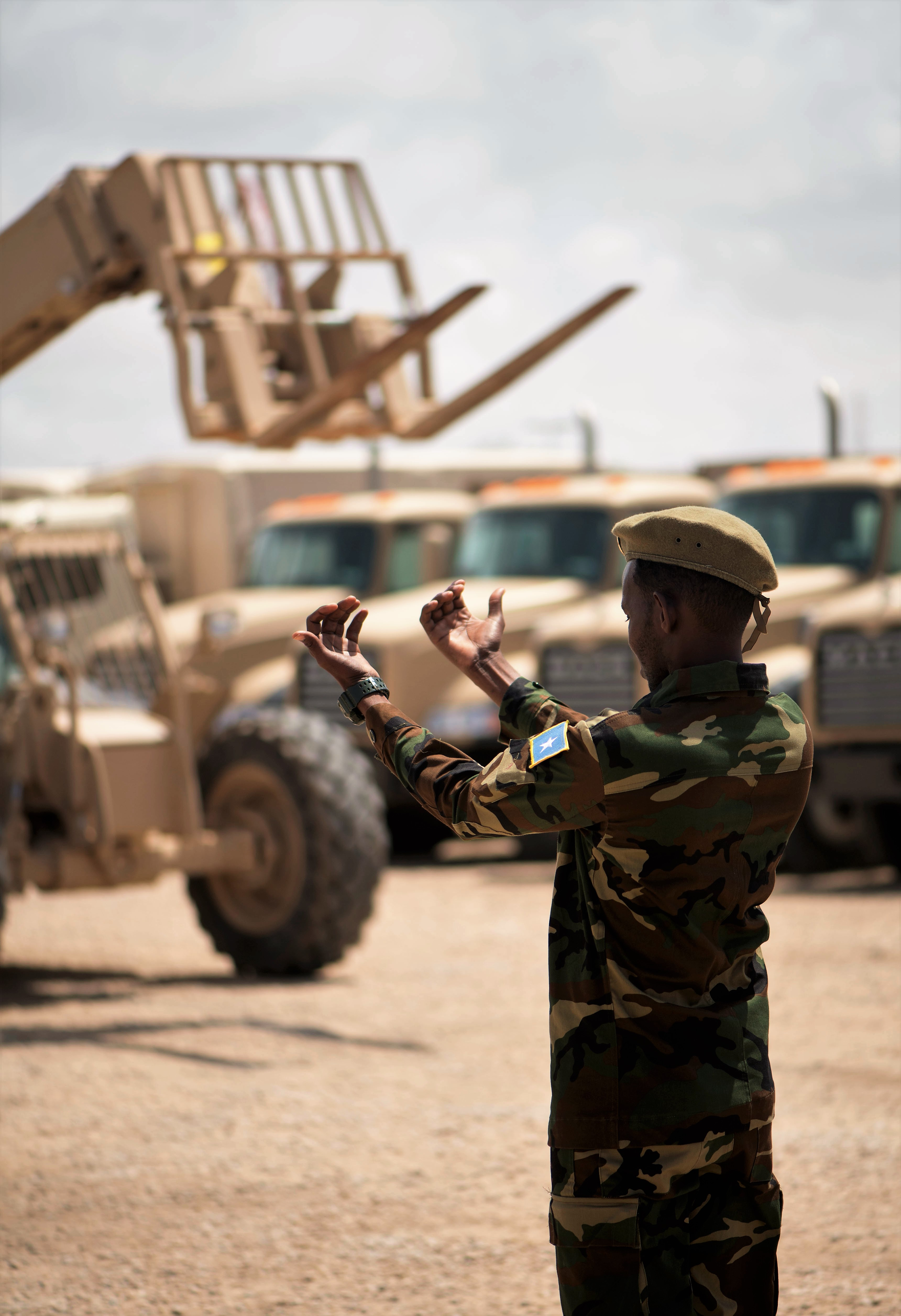 A Somali national army soldier gives directions to a forklift operator during a skills demonstration during a logistics course graduation ceremony.   Soldiers from Somali's special forces DANAB battalion spent 14 weeks training with the U.S. 10th Mountain division on the importance of logistical operation as well as the operation and maintenance of heavy equipment.  (Photo by MC2 (SW/AW) Evan Parker. Released)