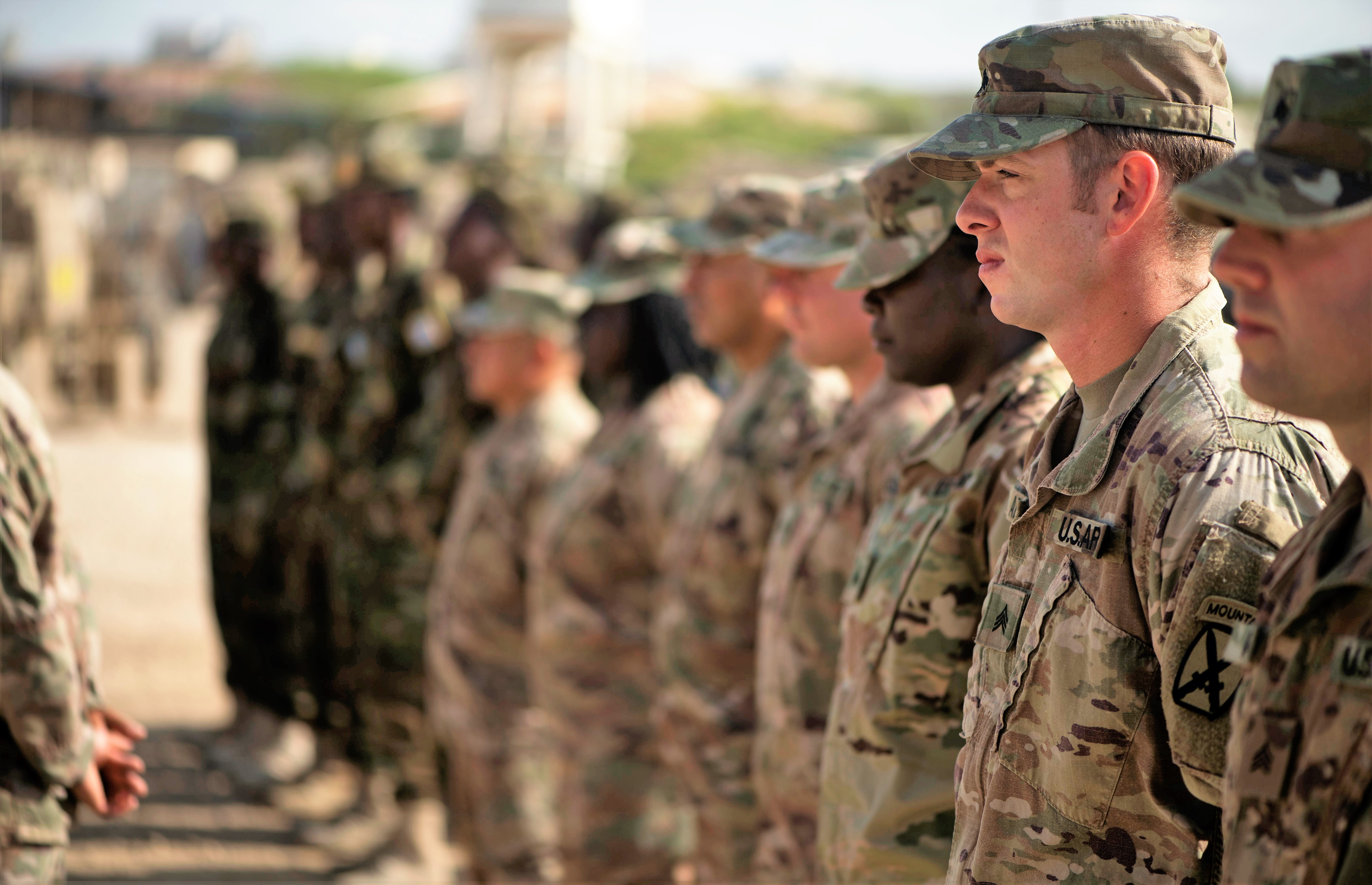U.S. Soldiers stand in formation during a logistics course graduation ceremony.   Soldiers from Somali's special forces DANAB battalion spent 14 weeks training with the U.S. 10th Mountain division on the importance of logistical operation as well as the operation and maintenance of heavy equipment.  (Photo by MC2 (SW/AW) Evan Parker. Released)