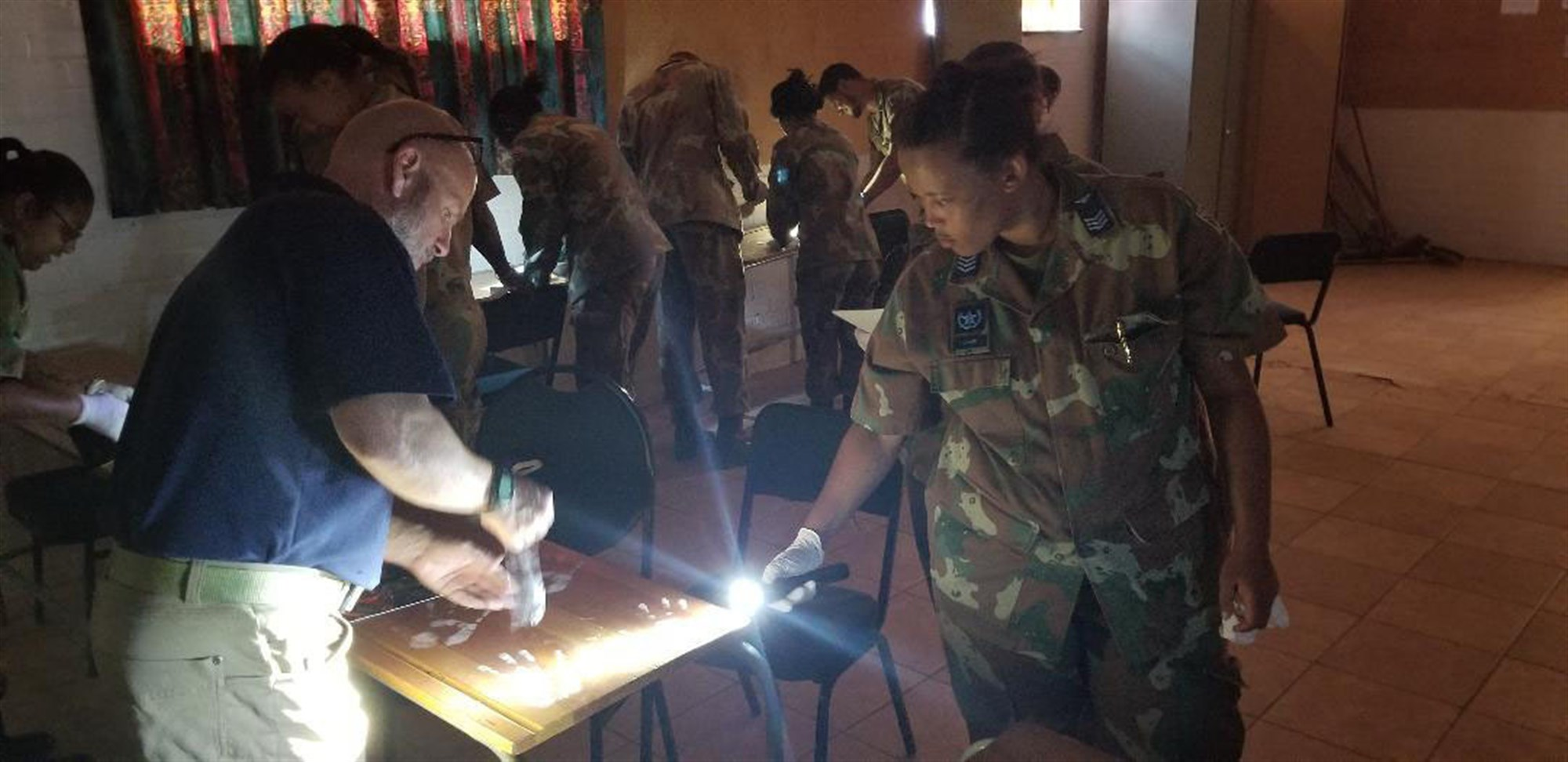 Naval Criminal Investigative Service Special Agent David Reid teaches evidence collection techniques to  South African Military Police Soldiers during an exchange visit on October 10, 2018. Soldiers from the New York Army National Guard also took  part in the  exchange program at the South African National Defense Forces Military Police School during an exchange visit there on Oct. 10-11, 2018. Twelve New York Army National Guard experts in civil support operations, military police, law enforcement, and self-defense took part in the exchange visit. ( U.S. Army National Guard phot by Sgt. Kristin Rosss)