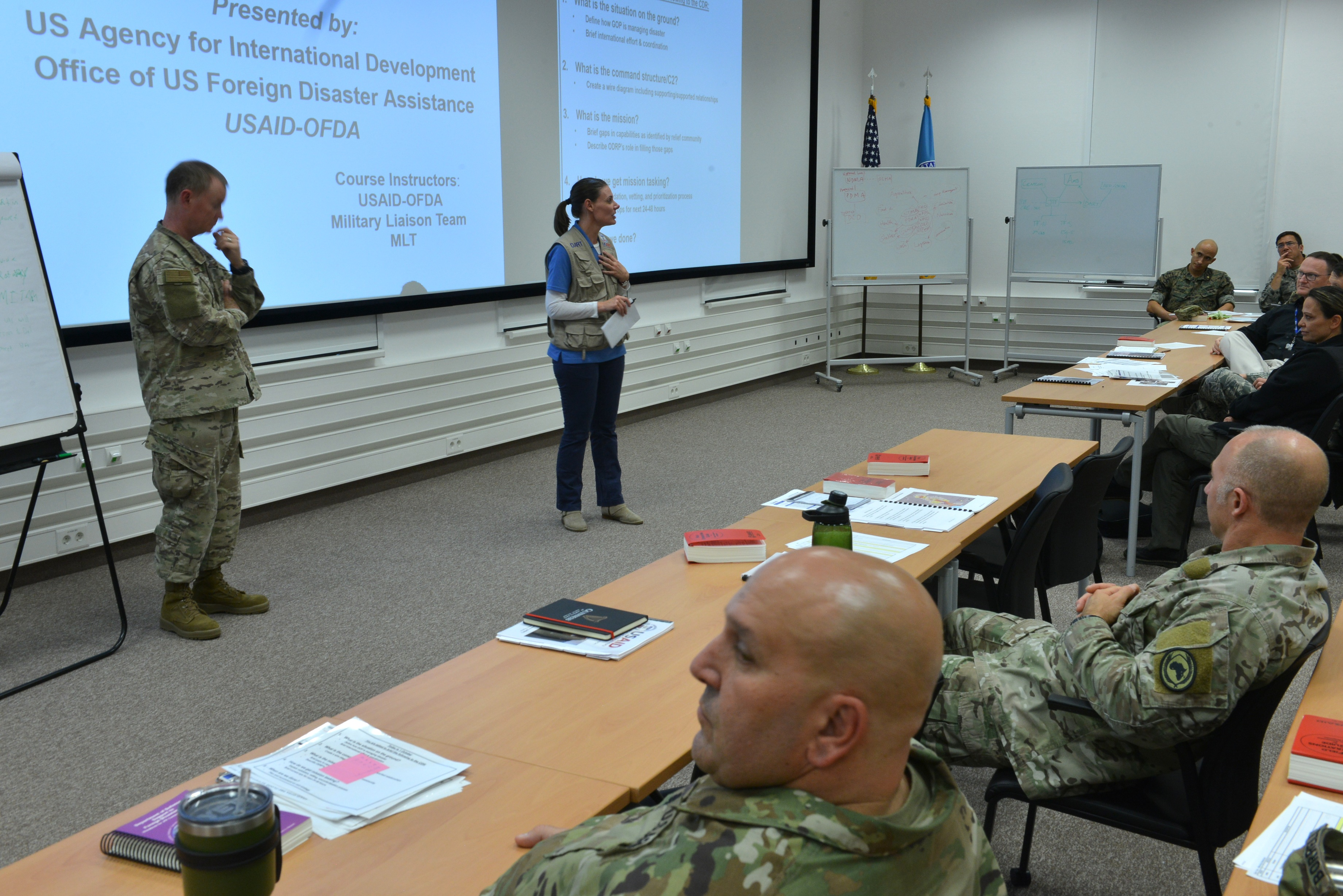 Air Force Brig. Gen. William West, Deputy Director of Operations, U.S. Africa Command, and Leigh Caraher, Lead Humanitarian Assistance Advisor to AFRICOM, address attendees of the Joint Humanitarian Operations Course, Oct. 4, 2018, at the AFRICOM Special Events Center.
