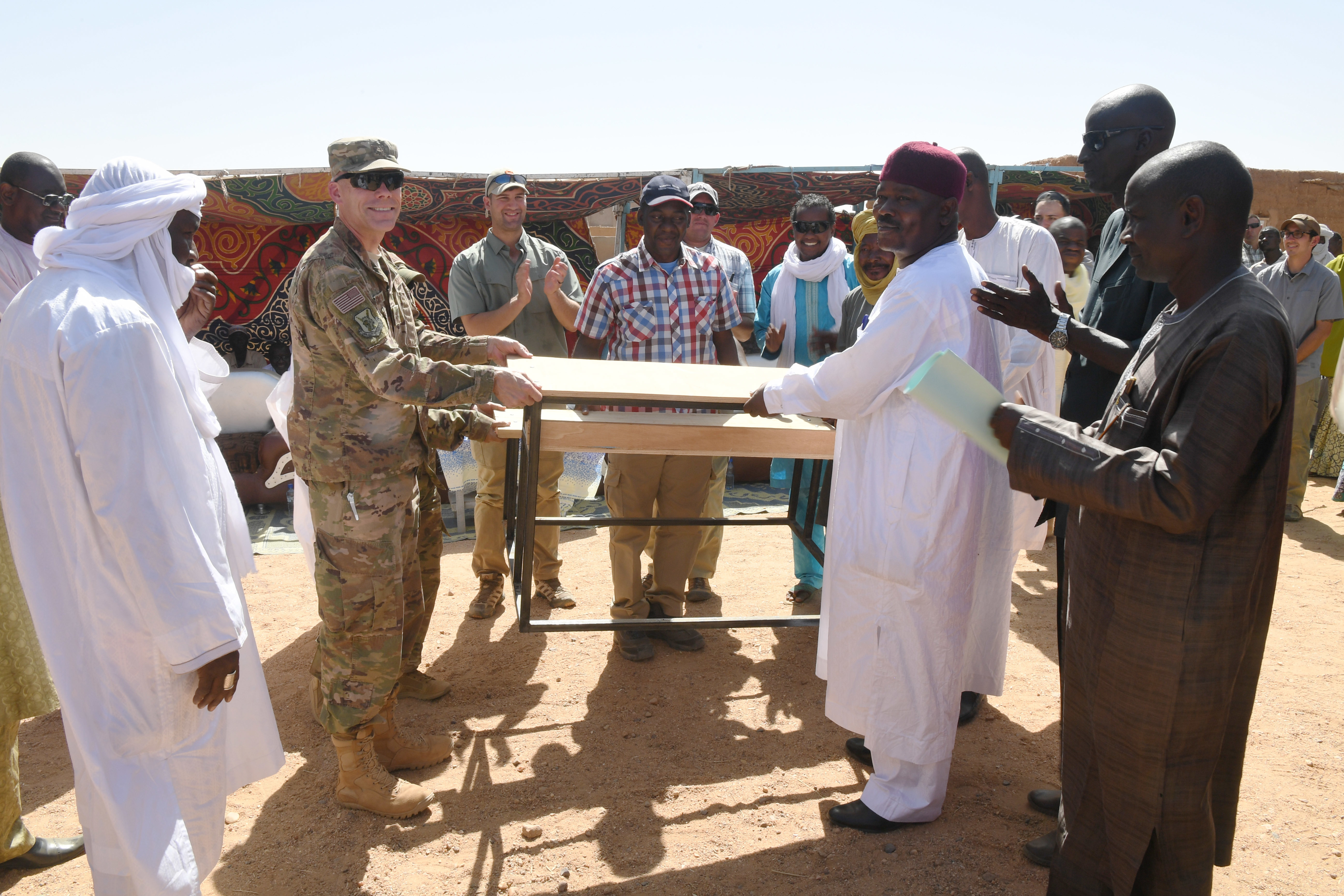 U.S. Air Force Lt. Col. Francis Tyson, 724th Expeditionary Air Base Squadron commander, presents a box of donated supplies to Ahmed Kosa, Agadez second vice mayor, during a ceremony in Agadez, Niger, Oct. 23, 2018. The ceremony