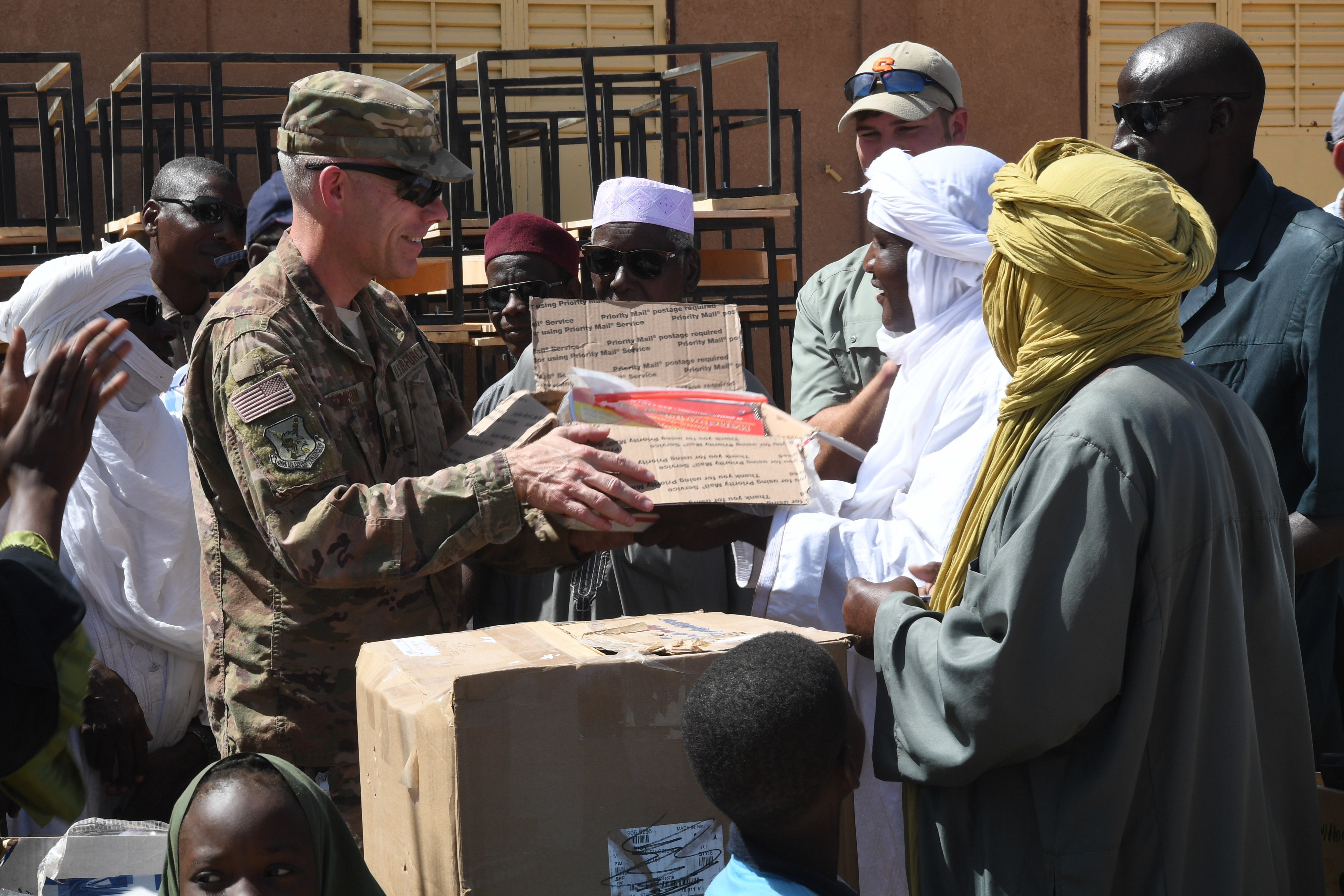 U.S. Air Force Lt. Col. Francis Tyson, 724th Expeditionary Air Base Squadron commander, presents a box of donated supplies to Ahmed Kosa, Agadez second vice mayor, during a ceremony in Agadez, Niger, Oct. 23, 2018. The ceremony recognized the first delivery of 1,000 desks that will be distributed to schools in the Agadez region. A donation of coloring books, writing utensils, paper, and other items gathered by the military community were also presented to the school. (U.S. Air Force photo by Tech. Sgt. Rachelle Coleman)