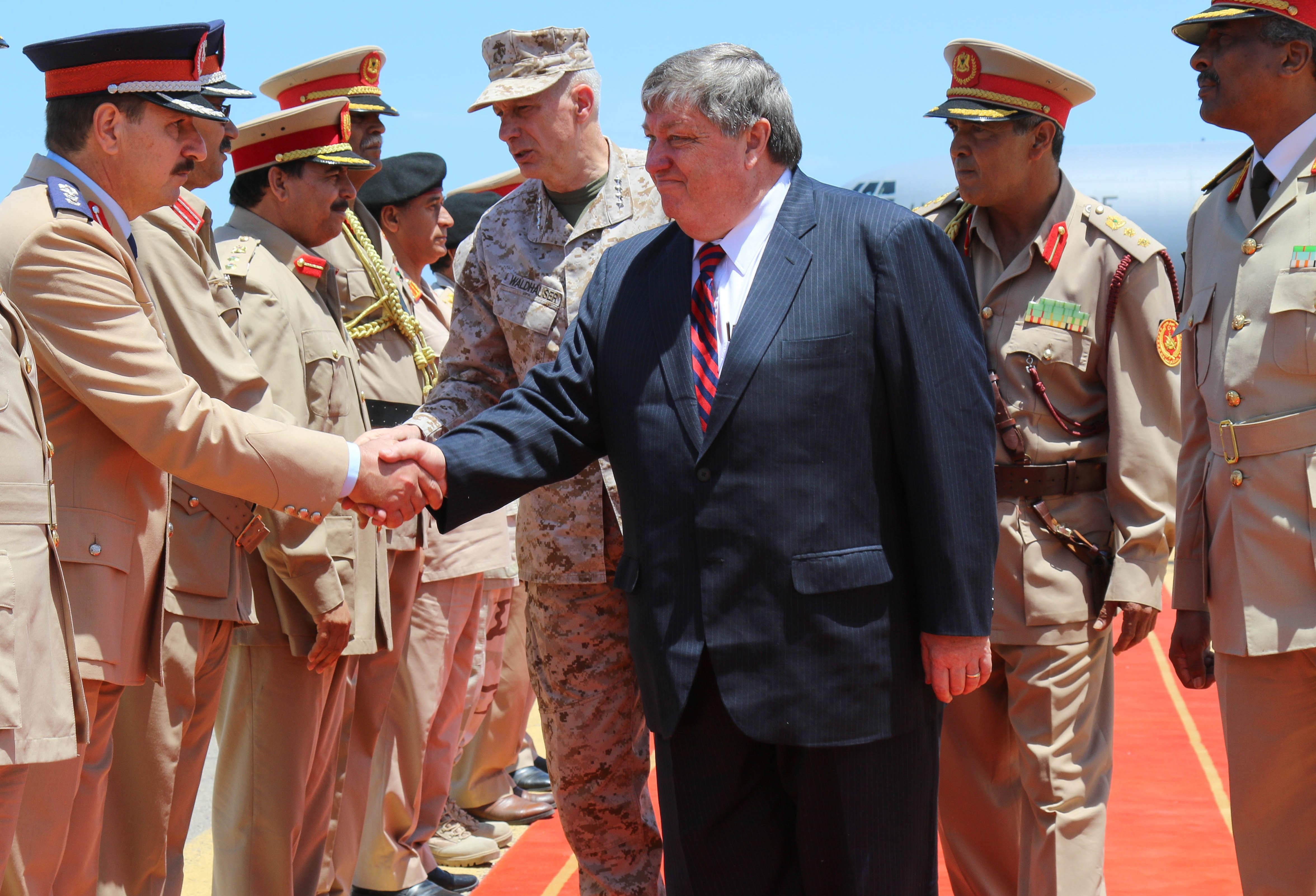 U.S. Marine Corps Gen. Thomas D. Waldhauser, commander, U.S. Africa Command and Amb. Peter Bodde, former U.S. Ambassador to Libya and current Chargé d'affaires a.i. at the Libya External Office, greet members of the Libyan Army during a visit to Libya in May 2017.