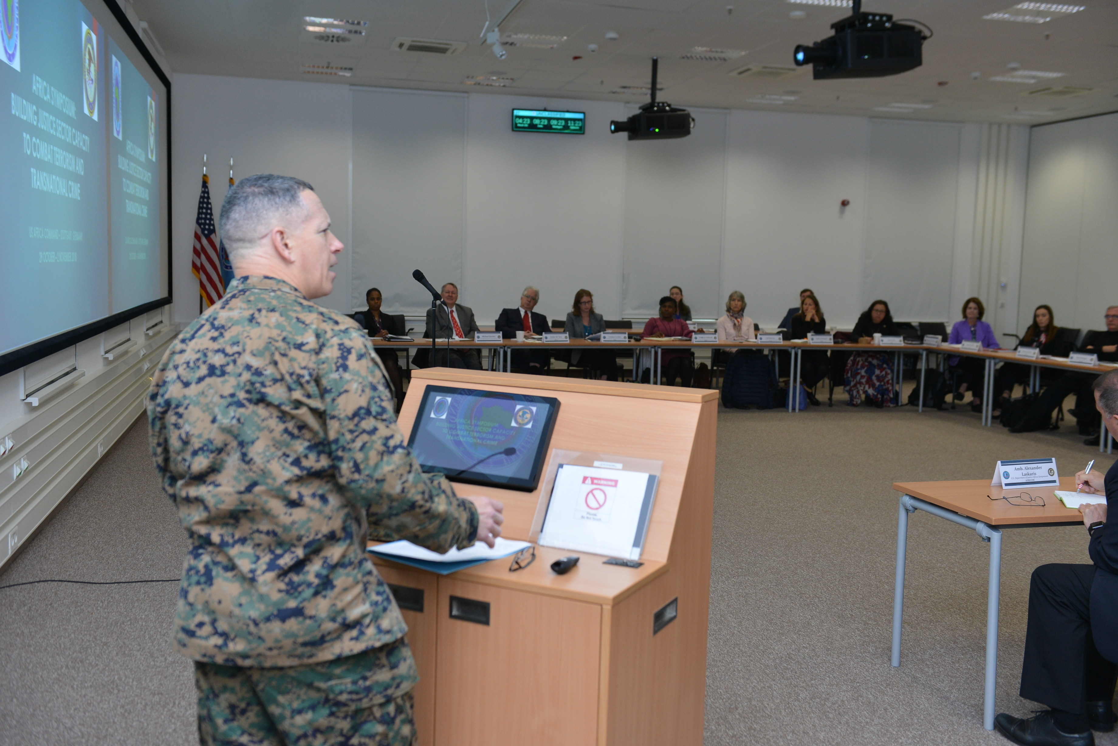 STUTTGART, Germany – Marine Col. Joseph Lore, Staff Judge Advocate, Office of Legal Counsel, U.S. Africa Command, addresses attendees of the first AFRCOM hosted DOJ Africa Symposium at the Kelly Barracks Special Events Center, Oct. 29, 2018.