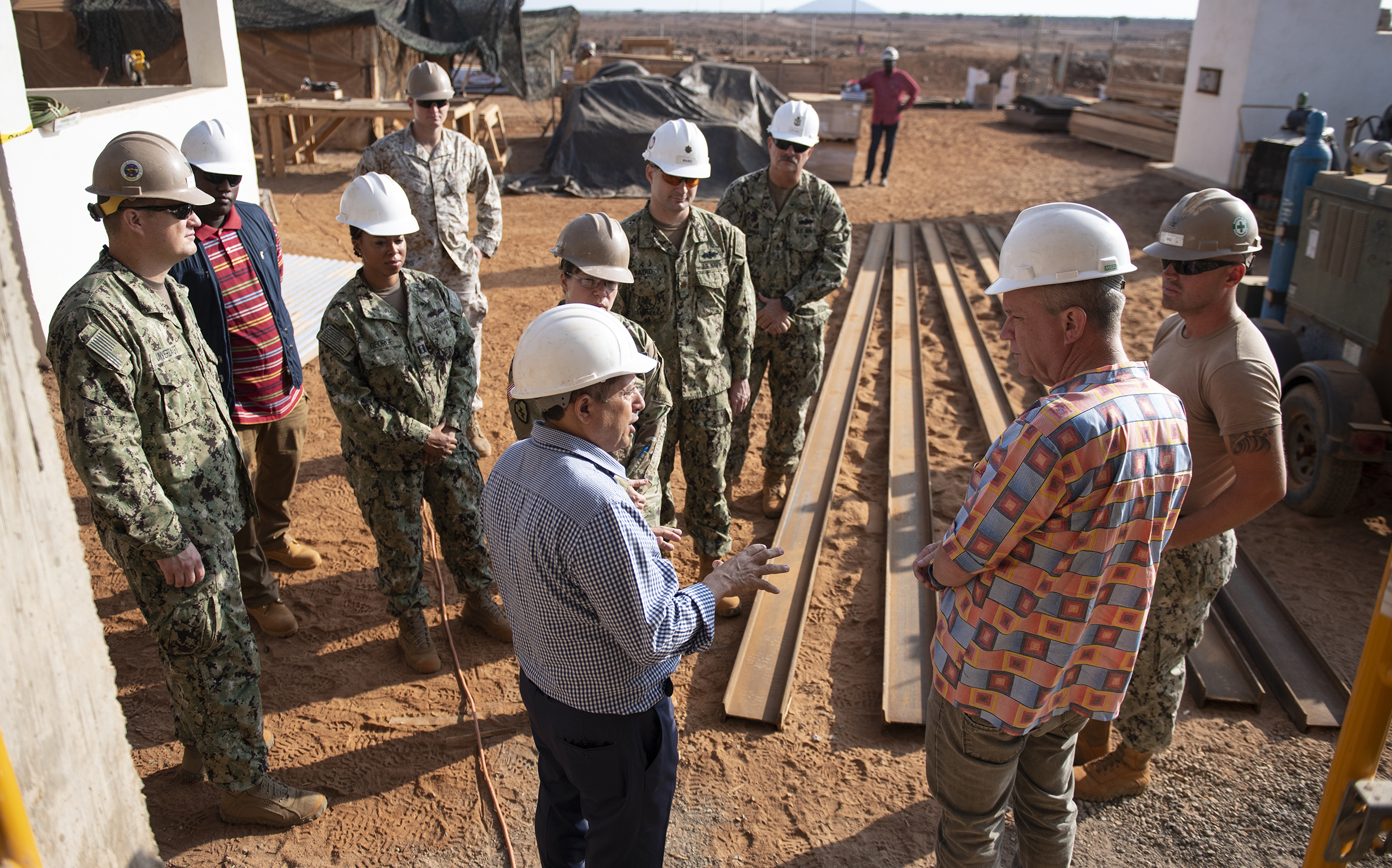 Amb. Larry André Jr., right, U.S. Ambassador to the Republic of Djibouti, speaks to an embassy official and U.S. Navy Seabees from Naval Mobile Construction Battalions 1 and 18, assigned to Combined Joint Task Force-Horn of Africa, Camp Lemonnier, Djibouti, during a visit to the construction site of the future Ali Oune, Djibouti, Women's Medical Clinic, Dec. 3, 2018. Slated for completion by January 2019, the clinic is intended to enhance the Ministry of Health for Djibouti's ability to provide basic medical, birth and after care to the Ali Oune village and its more than 1,000 residents and rural neighbors. (U.S. Air Force photo by Tech. Sgt. Shawn Nickel)
