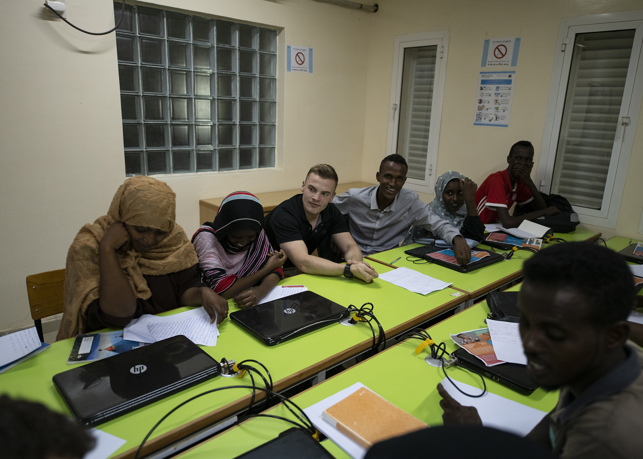 "U.S. Army Spc. Tracey Shelly, a civil affairs specialist, 403rd Civil Affairs Battalion, Combined Joint Task Force-Horn of Africa, Camp Lemonnier, Djibouti, works with students during the first-ever English Discussion Group (EDG) in the neighborhood of Balbala, Djibouti, Nov. 29, 2018.  The EDG serves as a ""language laboratory"" in which students develop practical linguistic and rhetorical skills through relationship building and information exchange. (U.S. Air Force photo by Tech. Sgt. Shawn Nickel)"