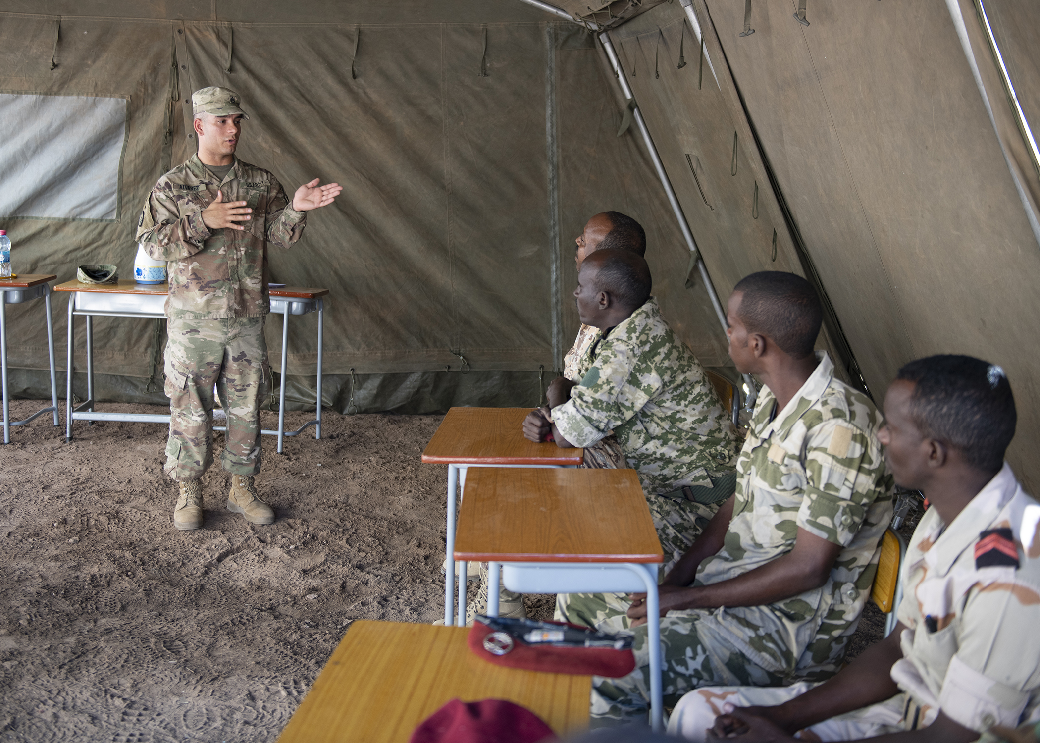 U.S. Army Staff Sgt. Jerry Alvarez, Combined Joint Task Force-Horn of Africa communications directorate NCO in charge, gives opening remarks during an Africa Data Sharing Network (ADSN), version two, information exchange with Djibouti Army (FAD) soldiers at FAD Headquarters, Djibouti, Dec. 26, 2018. The ADSN works as an internal network that the African Union Mission in Somalia troop-contributing countries can use to communicate and share information amongst each other. (U.S. Air Force photo by Tech. Sgt. Shawn Nickel)