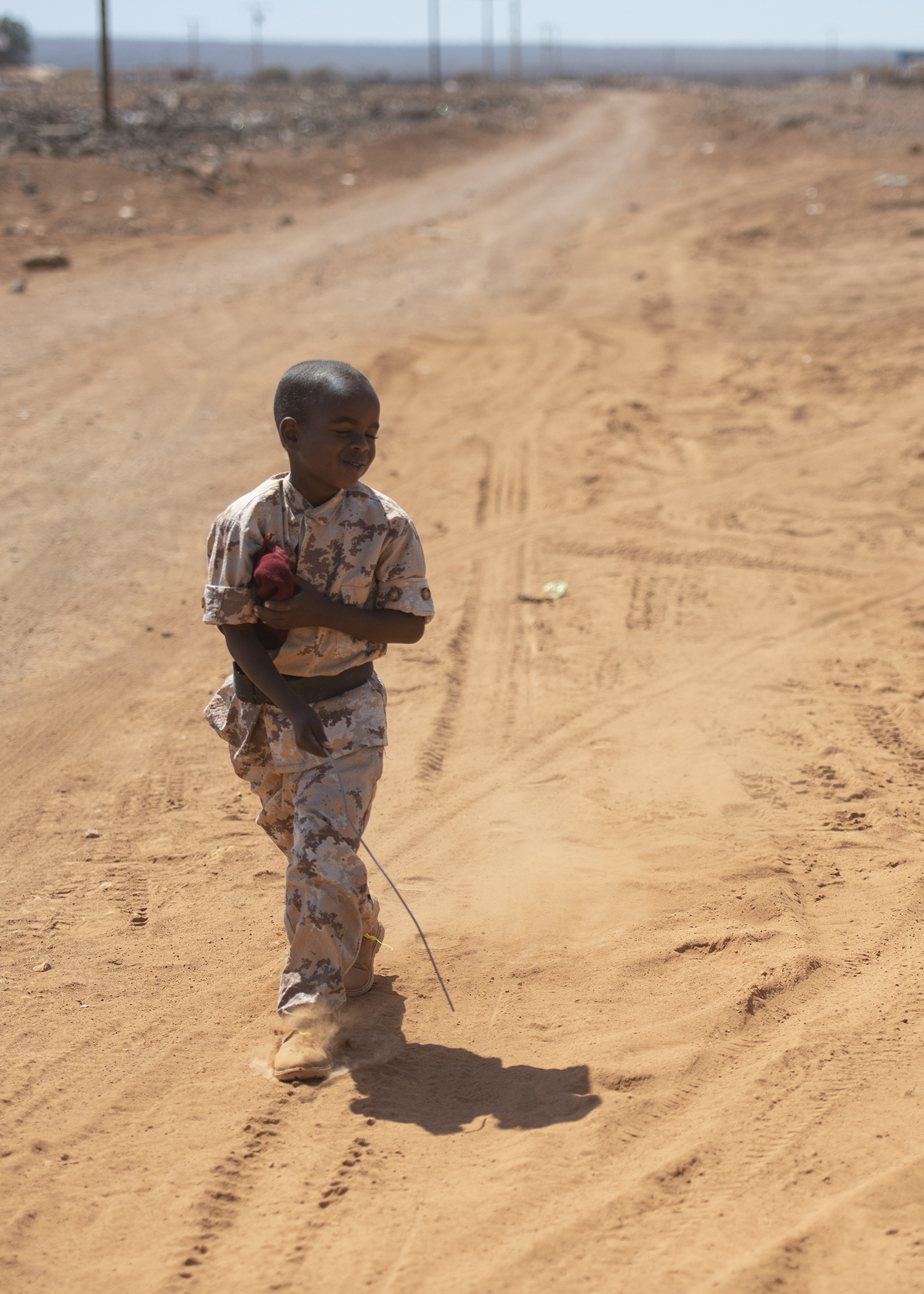 A Djiboutian youth dressed in military-style uniform plays along the road during the Ali Oune Medial Clinic ribbon cutting ceremony in Ali Oune, Djibouti, Jan. 31, 2019. The clinic, which salutes a U.S. Navy Seabee, from Naval Mobile Construction Battalion 1, have been working to complete for five months, is intended to enhance the Ministry of Health for Djibouti's ability to provide basic medical, birth and after care to the Ali Oune village and its more than 1,000 residents and rural neighbors. (U.S. Air Force photo by Tech. Sgt. Shawn Nickel)