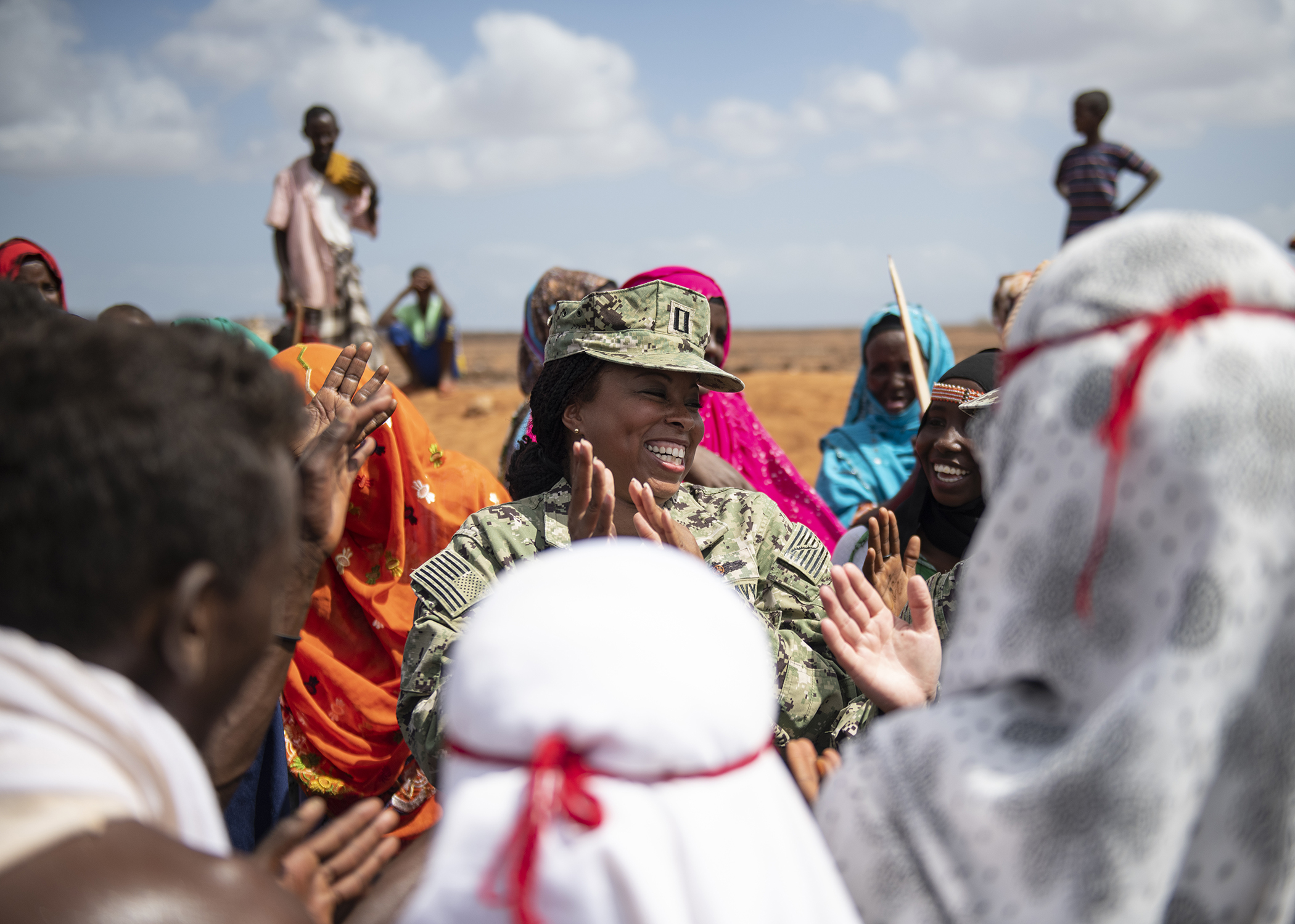 U.S. Navy Lt. Mellany George, an engineering project manager assigned to Combined Joint Task Force-Horn of Africa (CJTF-HOA), laughs as she dances with Djiboutian citizens before the Ali Oune Medial Clinic ribbon cutting ceremony in Ali Oune, Djibouti, Jan. 31, 2019. The clinic, which U.S. Navy Seabees from Naval Mobile Construction Battalion 1, assigned to CJTF-HOA, have been working to complete for five months, is intended to enhance the Ministry of Health for Djibouti's ability to provide basic medical, birth and after care to the Ali Oune village and its more than 1,000 residents and rural neighbors. (U.S. Air Force photo by Tech. Sgt. Shawn Nickel)