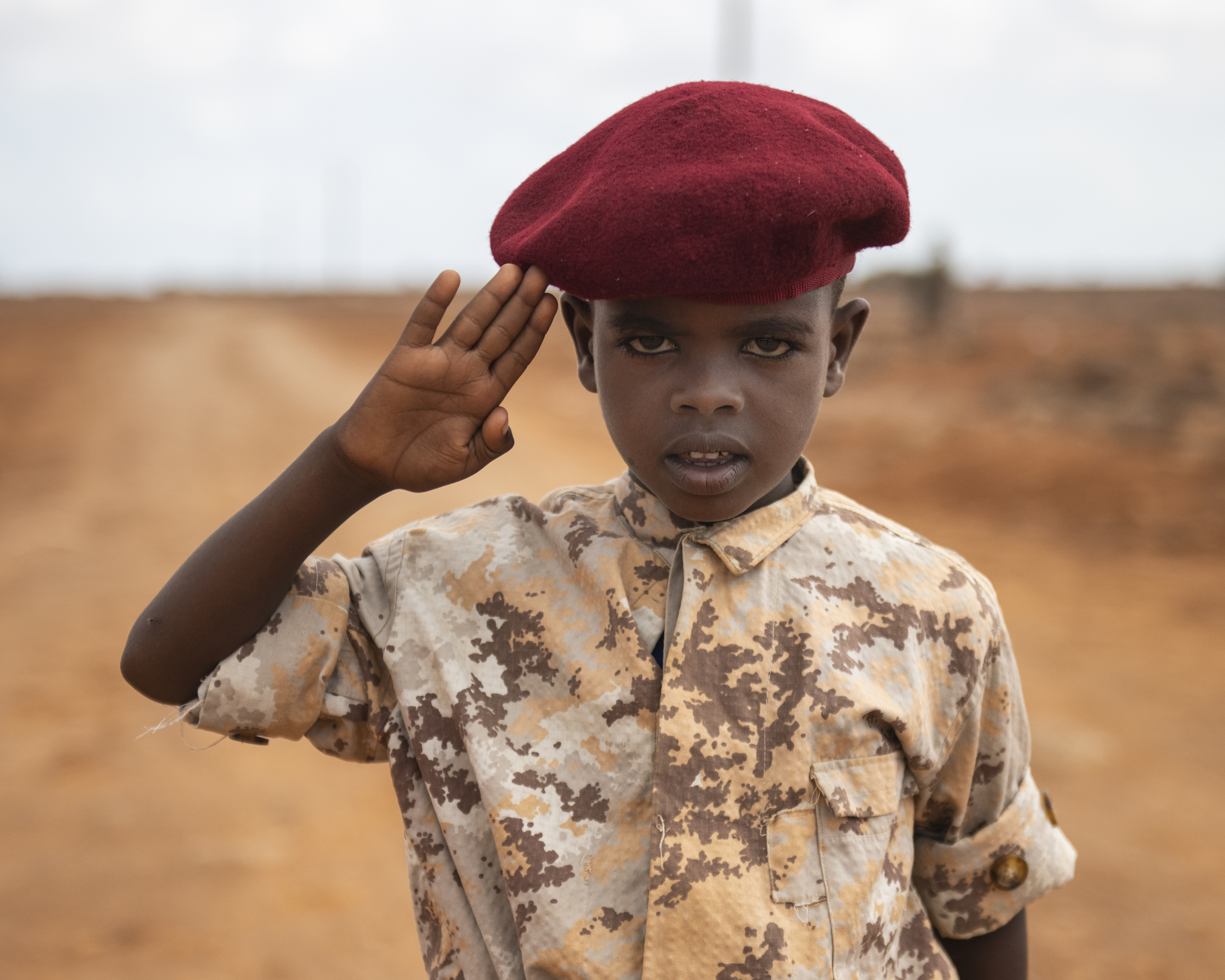 A Djiboutian youth dressed in military-style uniform salutes a U.S. Navy Seabee, from Naval Mobile Construction Battalion 1, Combined Joint Task Force - Horn of Africa, during the Ali Oune Medial Clinic ribbon cutting ceremony in Ali Oune, Djibouti, Jan. 31, 2019. The clinic, which the Seabees have been working to complete for five months, is intended to enhance the Ministry of Health for Djibouti's ability to provide basic medical, birth and after care to the Ali Oune village and its more than 1,000 residents and rural neighbors. (U.S. Air Force photo by Tech. Sgt. Shawn Nickel)