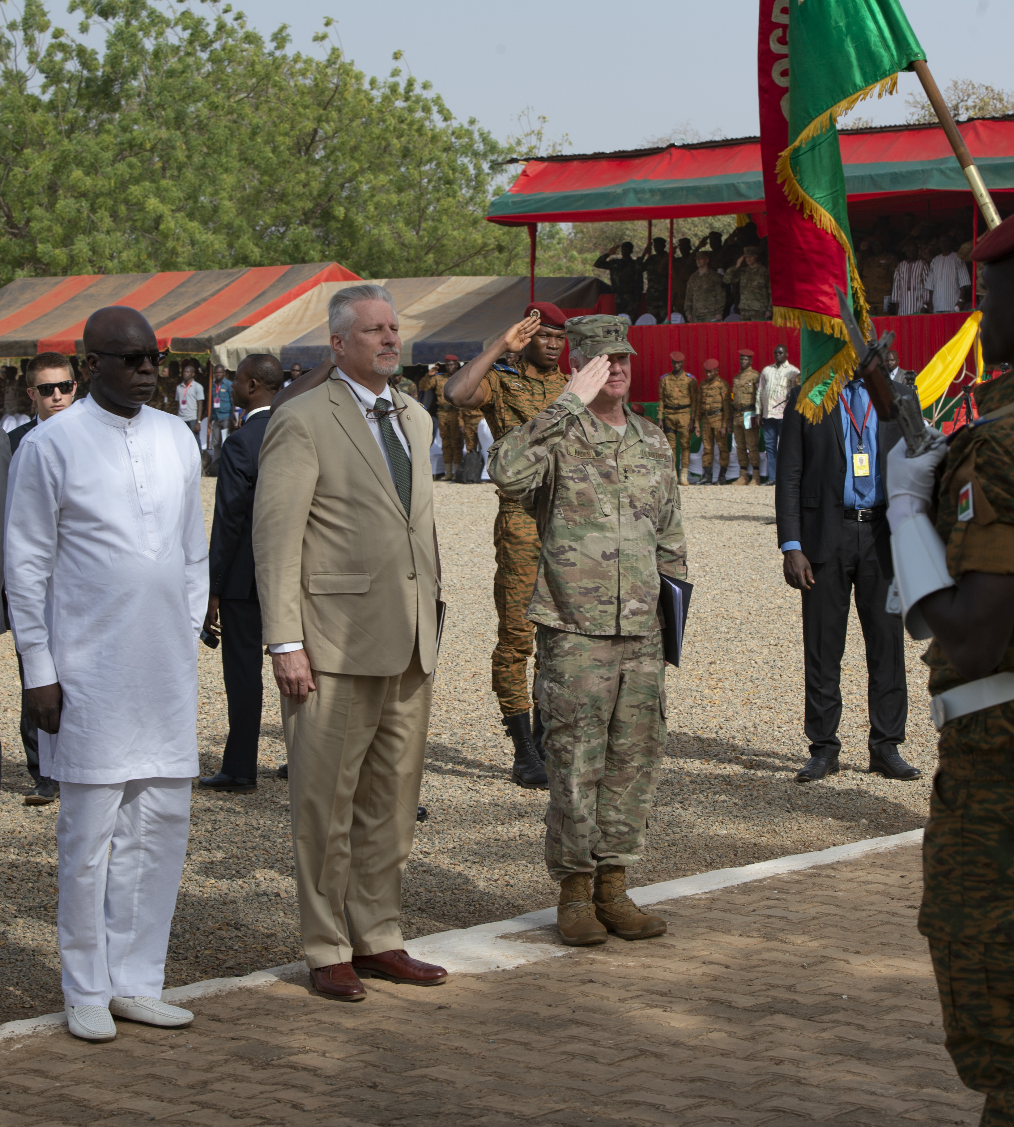 Minister of Defense and Veteran affairs, Chèrif Sy (left), U.S. Ambassador to Burkina Faso, Andrew Young, and U.S. Air Force Maj. Gen. Mark Hicks, Commander, Special Operations Command Africa (Right), render honors during a pass and review portion of the opening ceremony to Flintlock 2019.  This year's exercise is being hosted by Burkina Faso with a key outstation in Mauritania. Flintlock 2019 builds the capacity of participating nations to support regional cooperation, security and interoperability. (U.S. Navy photo by MC2 (SW/AW) Evan Parker / released)