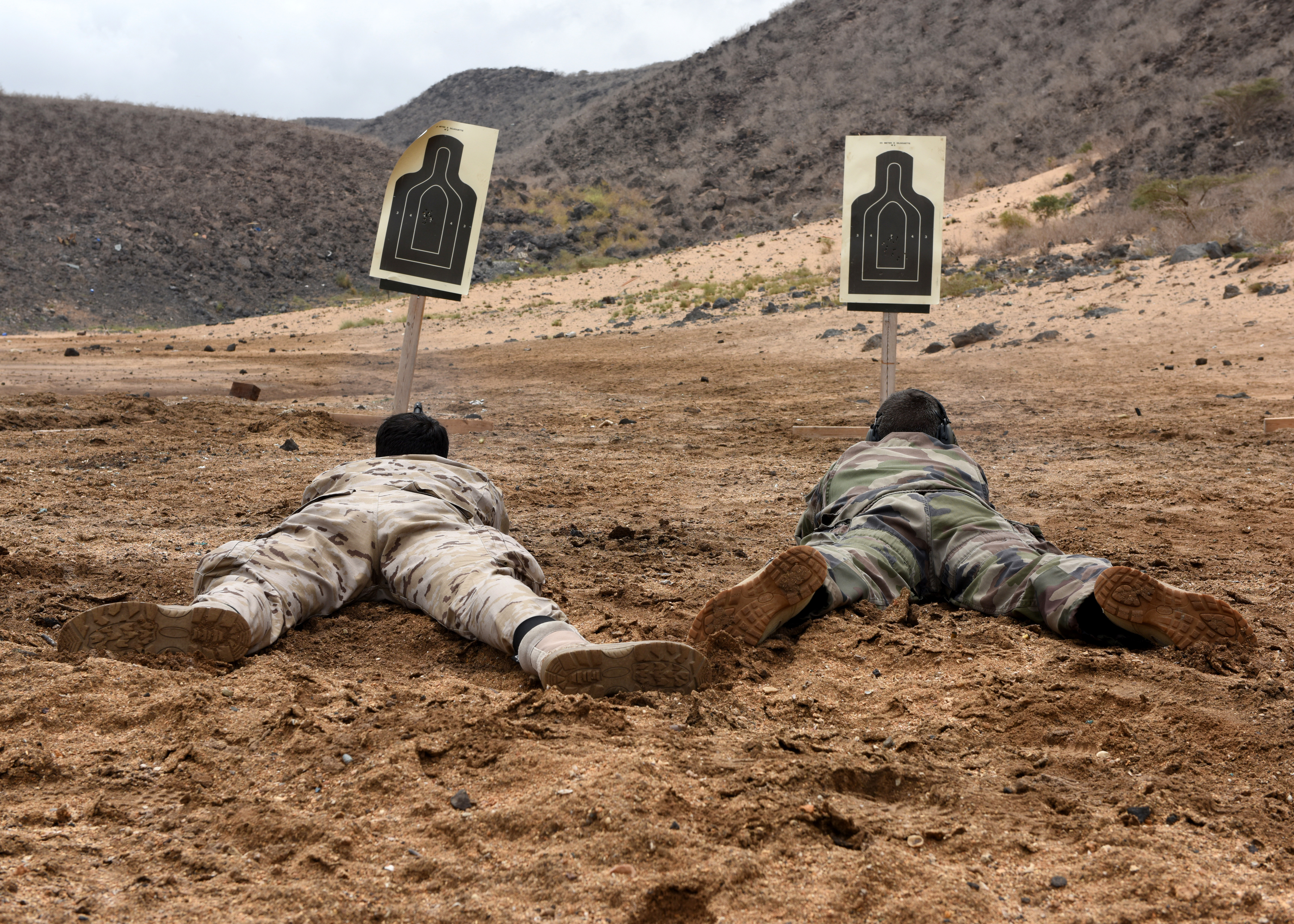 Combined Joint Task Force-Horn of Africa foreign liaison officers from Spain and France shoot targets from a prone position using Beretta M9 pistols during weapons familiarization at the Djibouti Range Complex, Arta, Djibouti, Feb. 16, 2019. The course gave the foreign liaison officers an insight on the Beretta M9 pistol and stance techniques used by U.S. military members. (U.S. Air Force photo by Staff Sgt. Franklin R. Ramos)