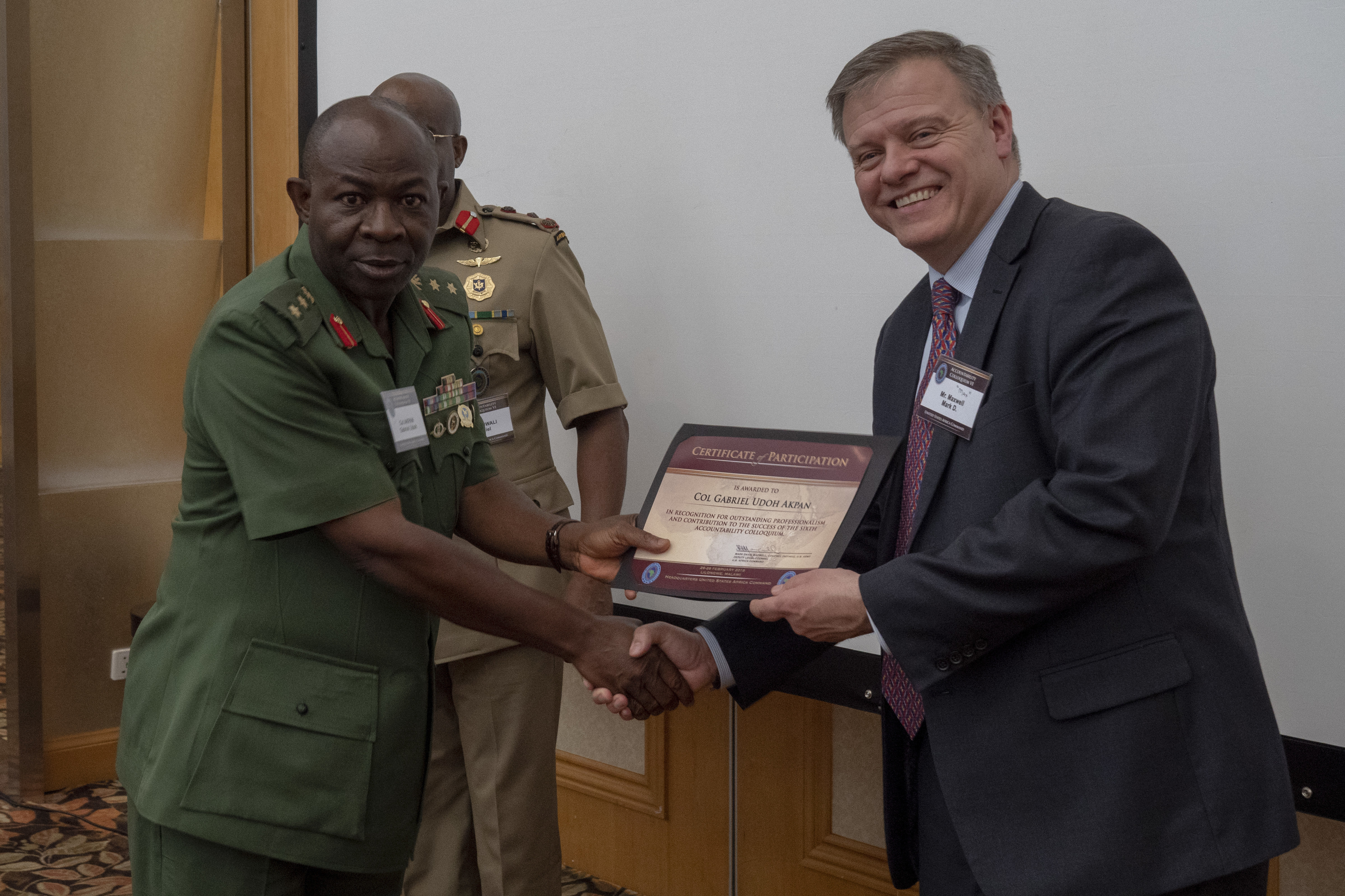 "Colonel Gabriel Udoh Akpan receives his Certificate of Participation from Mr. Mark D. ""Max"" Maxwell on the final day of the Accountability Colloquium VI in Lilongwe, Malawi, on February 28, 2019. The Accountability Colloquium is an annual event hosted by United States Africa Command's Office of Legal Counsel that seeks to create a collaborative forum for military commanders and their legal advisors to exchange information on topics related to African military operations. This iteration featured over 80 participants from 30 African nations. (DoD Photo by U.S. Army Sergeant Edward A. Salcedo)"