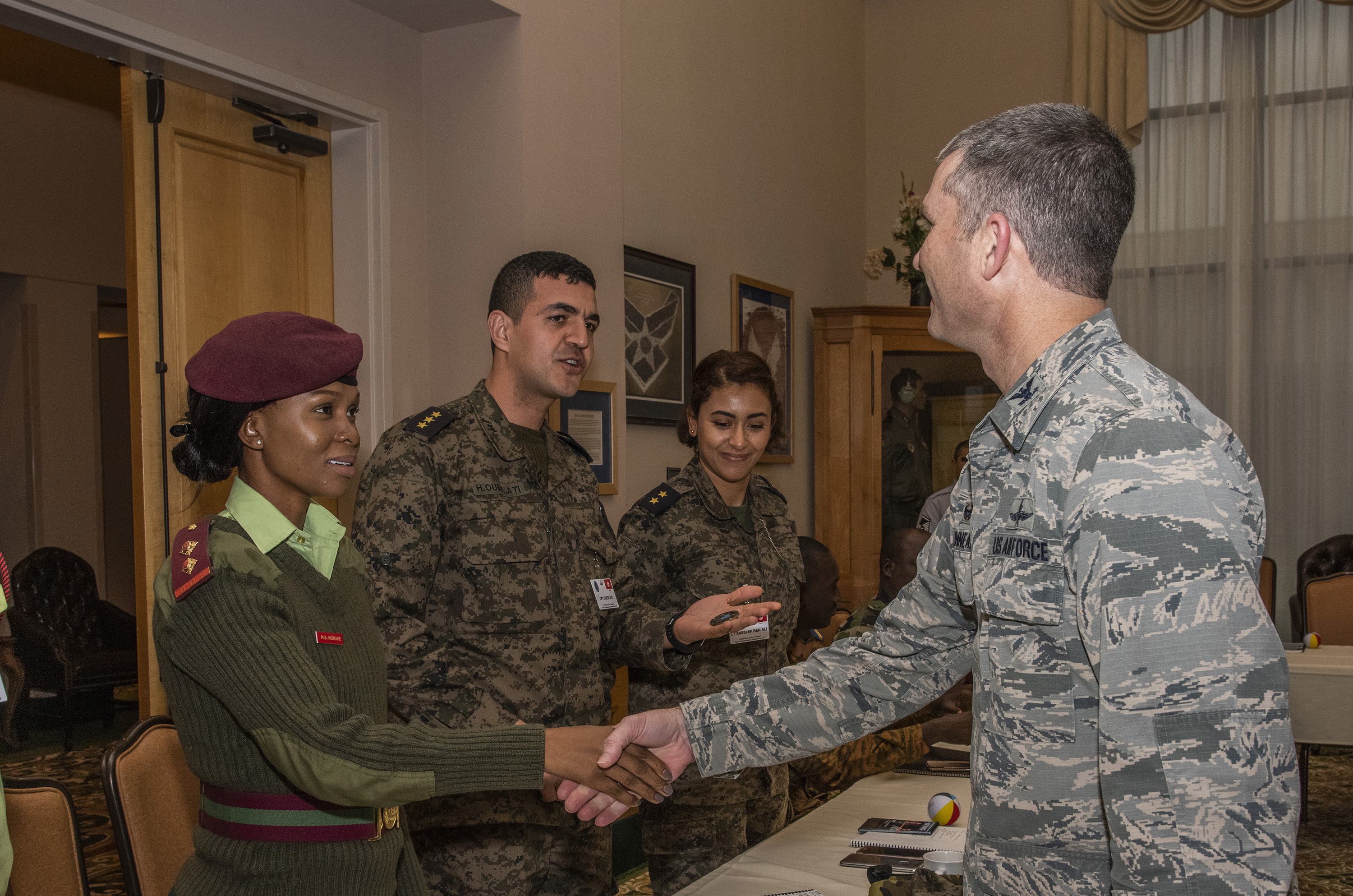 Botswana Defense Force Lt. Matshidiso Morake receives a coin from Col. Harold Linnean, 960th Cyberspace Wing vice commander duing a visit to Joint Base San Antonio-Lackland, Texas, Feb. 28.
