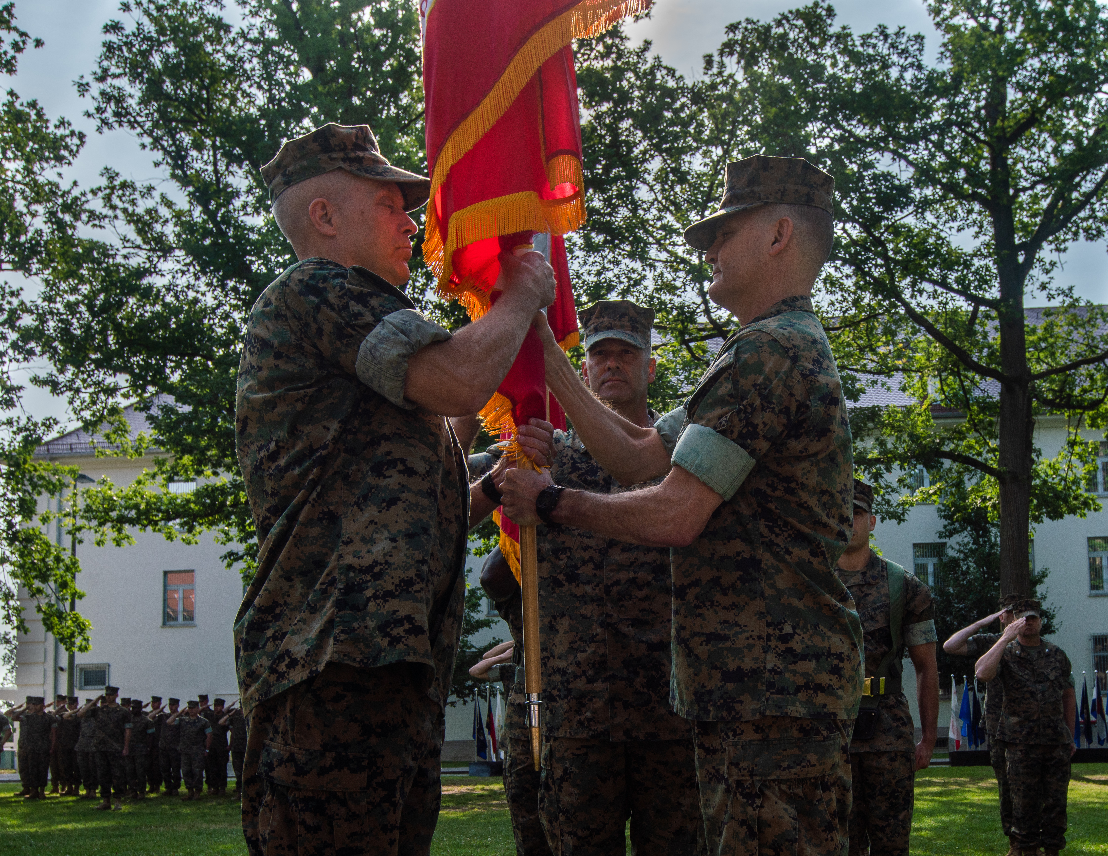 Major General Patrick J. Hermesmann , the incoming commander of Marine Forces Europe and Africa, receives the organizational colors from Maj. Gen. Russell A.C. Sanborn, the outgoing commander, during the change of command ceremony on the Devil Dog Field on Panzer Kaserne in Boeblingen, Germany, July 9, 2019. Sanborn, who commanded MARFOREUR/AF since July 2017, presided over several initiatives that grew the headquarters as a dynamic warfighting institution, to include increasing NATO capacity for allied amphibious operations; enhanced naval and amphibious integration into plans, operations and exercises; the expansion of the Marine Corps cold-weather and mountain-warfare rotational training presence in Norway's high north; and responsibility for US forces participating in Exercise Trident Juncture 2018, the largest NATO military exercise since the end of the Cold War. (U.S. Marine Corps photo by Lance Cpl. Menelik Collins/Released)