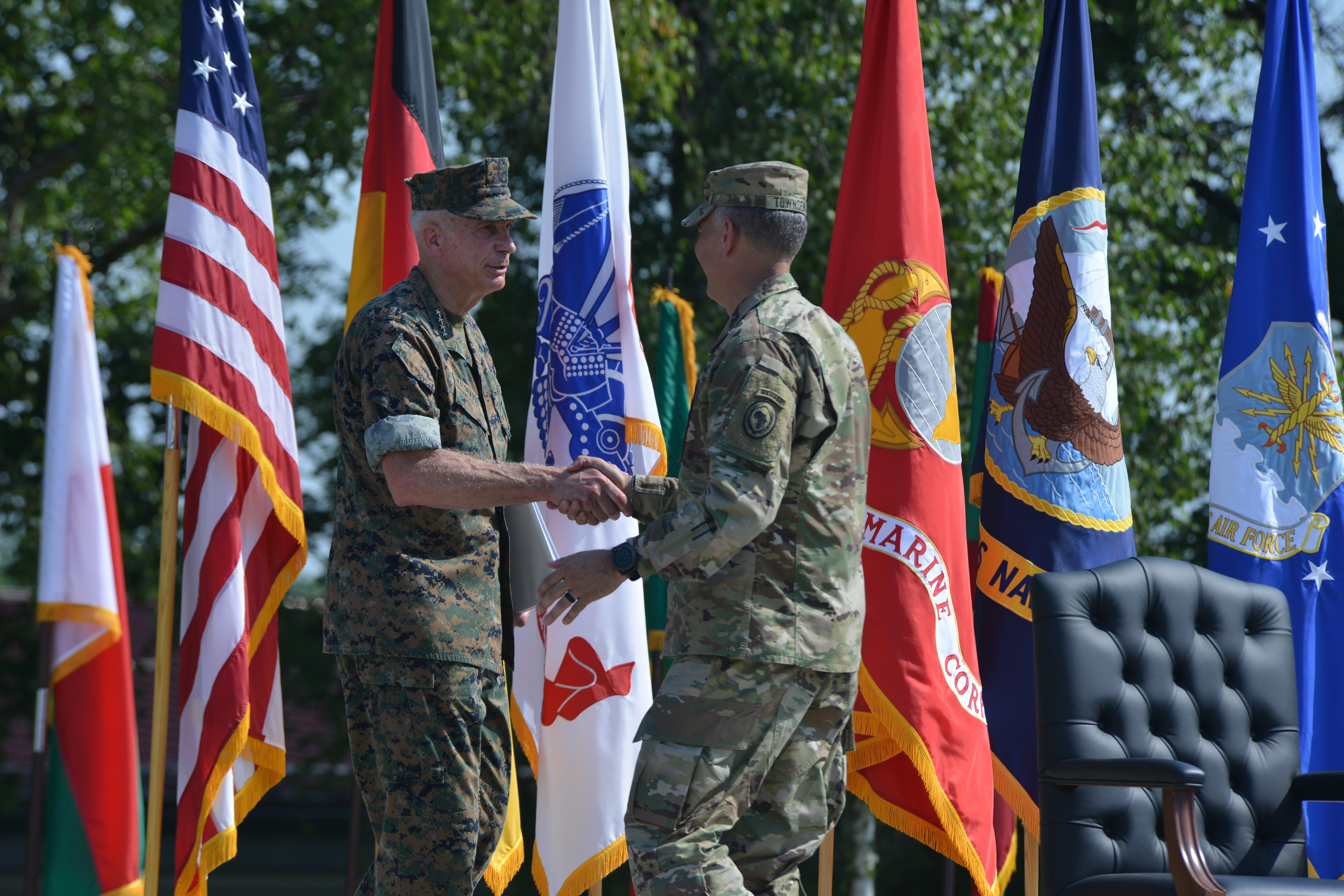 Marine Corps Gen. Thomas D. Waldhauser, outgoing commander, shakes hands with Army Gen. Stephen J. Townsend, incoming commander, during the AFRICOM change of command ceremony at Patch Barracks in Stuttgart, Germany, July 26, 2019. AFRICOM is one of six of the U.S. Defense Department's geographic unified commands and is responsible to the Secretary of Defense for military relations with African nations, the African Union, and African regional security organizations. (U.S. Army photo by Staff Sgt. Grady Jones/Released)