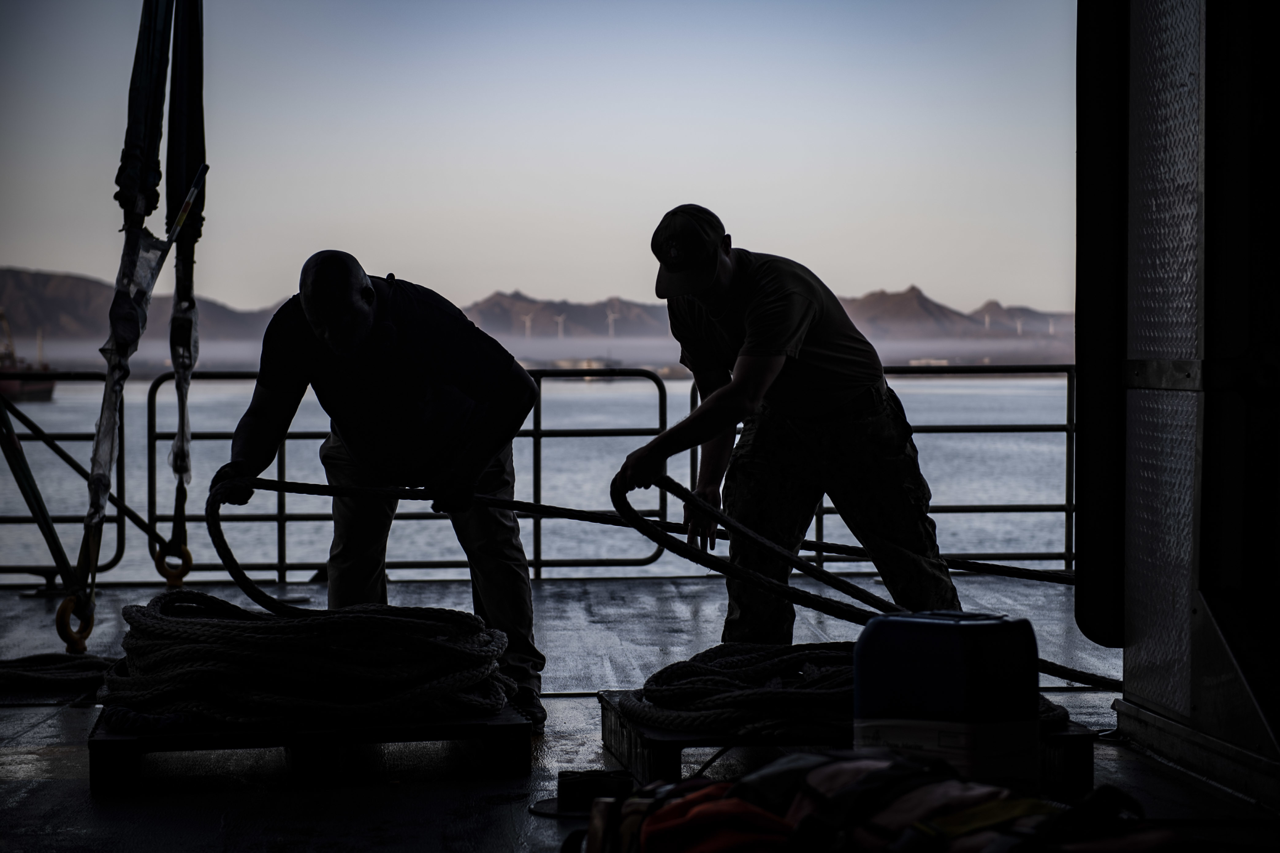 190810-N-JI086-0038 MINDELO, Cabo Verde (Aug. 10, 2019) A Sailor and Civil Service mariner heave line as the expeditionary fast transport ship USNS Carson City (T-EPF 7) departs Mindelo, Cabo Verde, Aug. 10, 2019. Carson City is deployed to the Gulf of Guinea to demonstrate progress through partnerships and U.S. commitment to West African countries through small boat maintenance assistance, maritime law enforcement engagement, and medical and community relations outreach. (U.S. Navy photo by Mass Communication Specialist 2nd Class Ford Williams/Released)