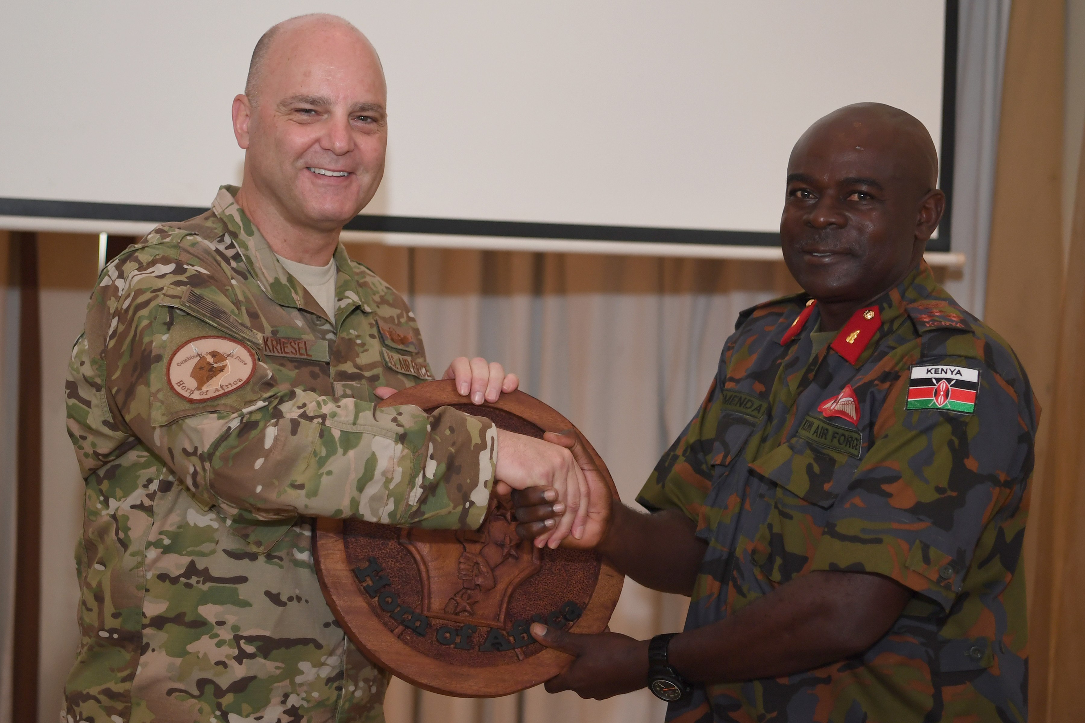 U.S. Air Force Brig. Gen. James R. Kriesel, Combined Joint Task Force—Horn of Africa deputy commanding general, exchanges gifts with Kenya Air Force Brigadier John Omenda, base commander at Laikipia Air Base, during the closing ceremony for African Partnership Flight Kenya 2019, Nanyuki, Kenya, August 25, 2019. The five-day event culminated with a Kenya Air Force-led exercise, Linda Rhino 2, using personnel recovery skills gained during the program. (U.S. Air Force photo by Master Sgt. Renae Pittman)