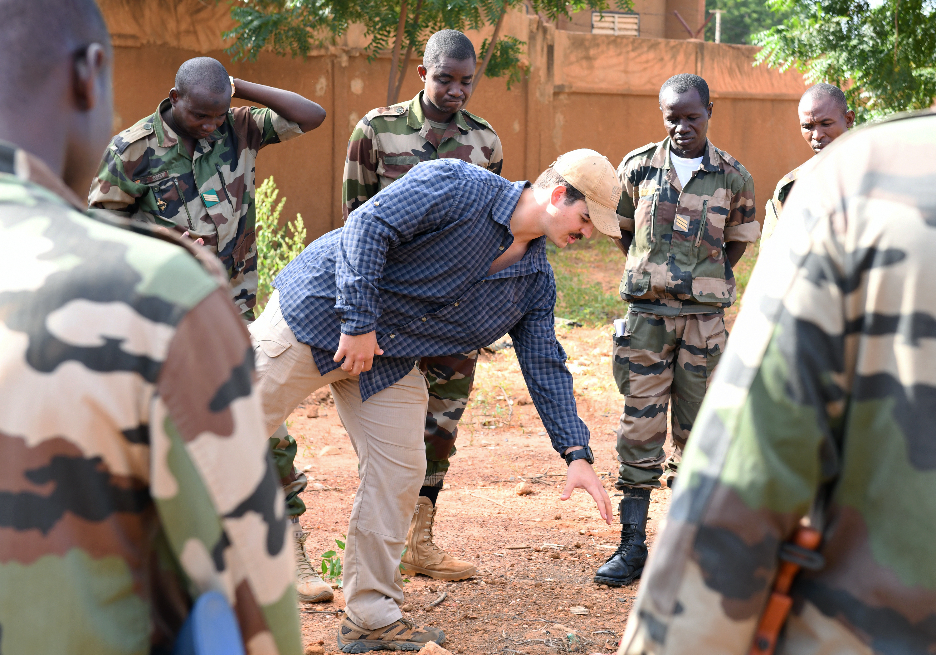 U.S. Air Force Senior Airman Caleb Love, 768th Expeditionary Air Base Squadron Explosive Ordnance Disposal team member, shows members of the Forces Armées Nigeriennes (Nigerien Armed Forces) Genie Unit disturbed earth, a common sign indicating improvised explosive devices, during an IED Awareness Course in Niamey, Niger, Oct. 11, 2019. During this week-long course, the FAN learned how to locate and react to an IED, how to set up a cordon and the procedures to clear the area. (U.S. Air Force photo by Staff Sgt. Alex Fox Echols III)