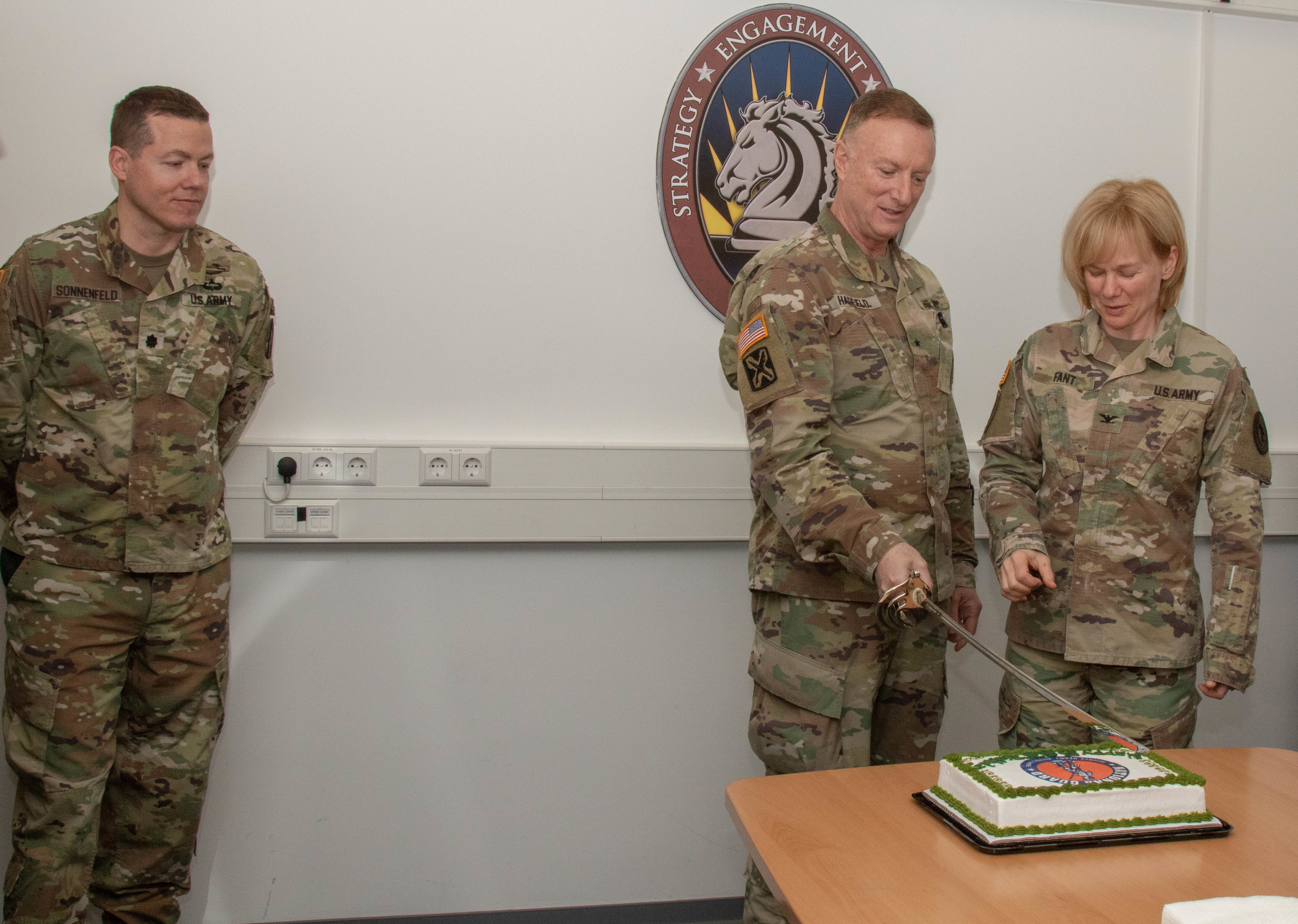National Guard Brig. Gen. Gregory J. Hadfield, AFRICOM deputy director for intelligence and Col. Patricia Fant, chief of the National Guard Integration, cut the cake to celebrate the National Guard's 383rd at Kelley Barracks Dec. 13.  Within AFRICOM, the National Guard plays several roles in promoting a stable security environment in Africa. One way this is accomplished is through the State Partnership Program, with 15 African nations partnered with 13 state National Guards. (U.S. Army photo by Staff Sgt. Flor Gonzalez/Released)
